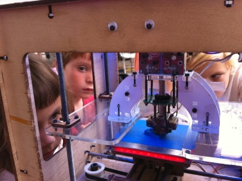 Kids surround a Makerbot.  Credit: Bre Pettis
